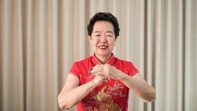 Chińska Azjatycka starsza kobieta w czerwonym kostiumowym nowego roku świętowania gescie zdjęcie stock