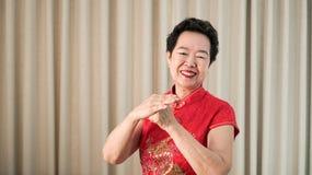 Chińska Azjatycka starsza kobieta w czerwonym kostiumowym nowego roku świętowania gescie zdjęcia stock