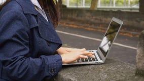 Chińska dziewczyna pisać na maszynie laptopem outside w zwolnionym tempie z zakończenie up rękami zbiory