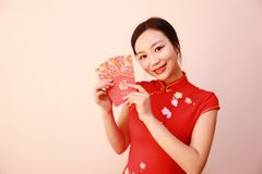 Chińska dziewczyna w tradycyjnego smokingowego cheongsam mienia paczek kobiety czerwonym chwycie z szczęsliwym pieniądze Obraz Stock