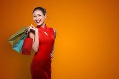 Chińska kobieta jest ubranym cheongsam chwyta torba na zakupy Zdjęcia Royalty Free