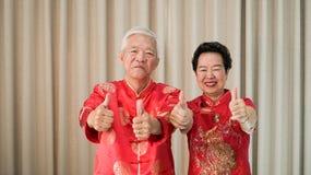 Chińska starsza starsza para w czerwonym kostiumowym kciuku w górę gesta zdjęcia royalty free