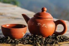 Chiński gliniany teapot i teacup z suchym herbacianym liściem Obrazy Royalty Free