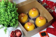 Chiński język: błogość, kij na cztery pomarańczowych tortach w pudełku z czerwoną kuchenną rękawiczką i czerwieni tkanina, zdojes obrazy stock