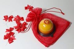 Chiński język: błogość, kij na pomarańczowym torcie na czerwonej tkaniny torbie i czerwień faborek na białej podłodze, fotografia stock