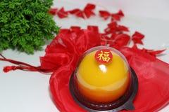Chiński język: błogość, kij na pomarańczowym torcie na czerwonej tkaniny torbie i za ostrość czerwonym faborku i zieleń liściu na zdjęcie stock