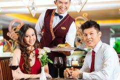 Chiński kelner porci gość restauracji w eleganckiej restauraci lub hotelu Zdjęcia Stock