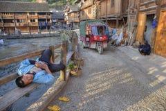 Chiński mężczyzna lying on the beach na ławka wśrodzie wioski ulica, Chiny Fotografia Royalty Free