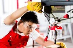 Chiński mężczyzna pracuje z musztruje wewnątrz fabrykę Fotografia Royalty Free