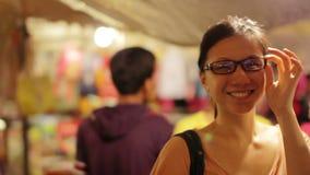 Chiński młoda kobieta zakupy przy azjatykcim noc rynkiem zbiory