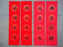 Chińskie kaligrafii przyśpiewki na czerwonym szczęsliwym papierze Fotografia Stock