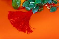 Chińskie nowy rok dekoracje na czerwonych błyskotliwość dekoracjach i tangerines, fotografia stock
