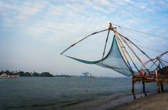 Chińskie sieci rybackie i mały statek przy dramatycznym zmierzchu nieba tłem Zdjęcie Stock