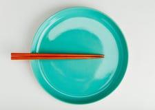 Chińskiego stylu chopsticks stawiający na zielonym naczyniu Obraz Royalty Free