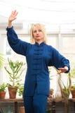 'chi' cinese del tai di arti marziali Donna che pratica disciplina di Taijiquan in una serra con i fiori immagini stock