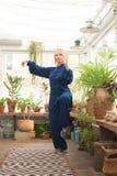 'chi' cinese del tai di arti marziali Donna che pratica disciplina di Taijiquan in una serra con i fiori immagine stock libera da diritti