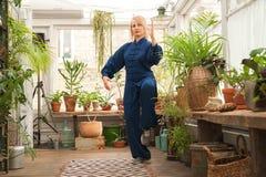 'chi' cinese del tai di arti marziali Donna che pratica disciplina di Taijiquan in una serra con i fiori fotografie stock libere da diritti