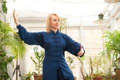 'chi' cinese del tai di arti marziali Donna che pratica disciplina di Taijiquan in una serra con i fiori immagini stock libere da diritti