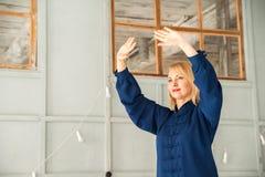 'chi' cinese del tai di arti marziali Donna che pratica disciplina di Taijiquan in una serra con i fiori fotografia stock