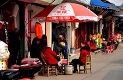 Chi Jiu πόλη, Κίνα: Γυναίκες και καταστήματα στην πόλης οδό Στοκ Φωτογραφία