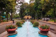 Ho Chi Minh city, Vietnam - December 2018: fountains in the park with flowerbeds, paths, green trees and yellow building. Chi minh city vietnam december 2018 royalty free stock photo