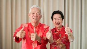 Chi?ska starsza starsza para w czerwonym kostiumowym kciuku w g?r? gesta zdjęcie royalty free