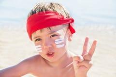 Chi sono io? Protezione solare & x28; lotion& x29 di abbronzatura; è sul fronte del ragazzo dei pantaloni a vita bassa prima dell Immagine Stock Libera da Diritti