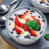 Chia与草莓、杏仁和巧克力曲奇饼面包屑,方形的格式的种子布丁 免版税图库摄影