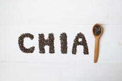 Chia frö Chia ord som göras från chiafrö med skeden som är full av chia på vit träbakgrund royaltyfria foton