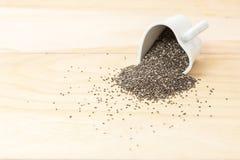Chia frö spiller ut ur slut för hjärtaformkopp upp på wood bakgrund Royaltyfri Fotografi