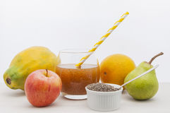 Chia and fresh fruit. A glass of fruit juice with chia surrounded by apple, papaya, orange and pear Stock Photos