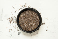 Chia grains on a white table. Chia grains in a black bowl on a white table Stock Image