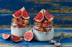 Chia milk pudding with granola and fresh sliced figs in the glass jars on the blue wooden kitchen table. Detox superfood breakfast Royalty Free Stock Image
