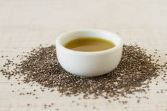 Chia oil and seeds for a healthy life style. Chia oil with seed on white wooden table background royalty free stock photo