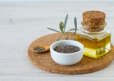 Chia oil and seeds for a healthy life style. Chia oil with seed on white wooden table background royalty free stock images