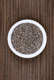 Chia on Plate. Chia seeds on white porcelain plate, wood background table Stock Photos