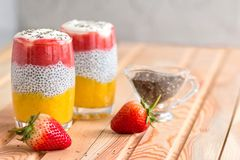 Chia pudding with mango, yogurt, chia, wild strawberry  in a glass  on the table laid by burlap. Healthy dessert,  super food royalty free stock photography