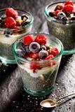 Chia-Pudding mit Zusatz von Himbeeren und von Blaubeeren in den Gläsern auf einem schwarzen Hintergrund, Konzept der gesunden Diä lizenzfreie stockfotos