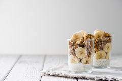 Chia pudding parfait, layered yogurt with banana, granola. Copy space Royalty Free Stock Photos