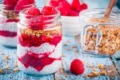 Chia pudding with raspberry sauce, granola and fresh raspberries. On rusic background Royalty Free Stock Photography