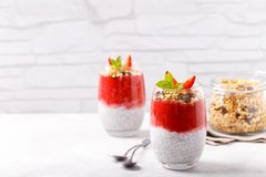 Chia pudding with strawberry sauce. Homemade granola on white rusic background stock photography