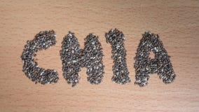Chia słowo robić od chia ziaren na drewnianym talerzu Fotografia Royalty Free