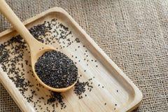 Chia-Samen auf einem hölzernen Löffel gegen Leinwandhintergrund Stockfotografie