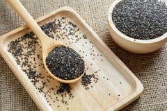 Chia-Samen auf einem hölzernen Löffel gegen Leinwandhintergrund Lizenzfreies Stockbild
