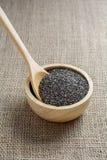 Chia-Samen in einer hölzernen Schale gegen Leinwandhintergrund Stockbild