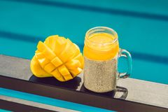 Chia seed pudding with almond milk and fresh mango topping on the background of the pool stock photography