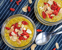 Chia seed puddings with saffron. Healthy homemade yellow chia seed puddings with saffron topped with goji berries and almonds and served in glass jars Royalty Free Stock Images