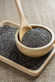 Chia seed in a wooden cup. Against burlap background stock photos
