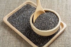 Chia seed in a wooden cup. Against burlap background royalty free stock image