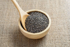 Chia seed in a wooden cup. Against burlap background royalty free stock photography